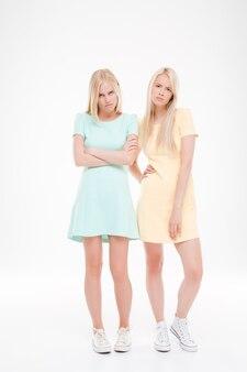 Foto von zwei empörten damen, die über einer weißen wand posieren und nach vorne schauen