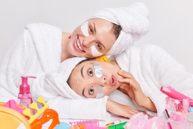Foto von zwei gemischten jungen frauen, die die köpfe in der nähe des tisches neigen, mit kosmetischen produkten, die flecken unter den augen anbringen