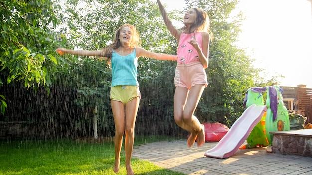 Foto von zwei glücklich lachenden schwestern in nasser kleidung, die unter wassertröpfchen aus dem gartenschlauch im garten tanzen. familie, die im sommer im freien spielt und spaß hat