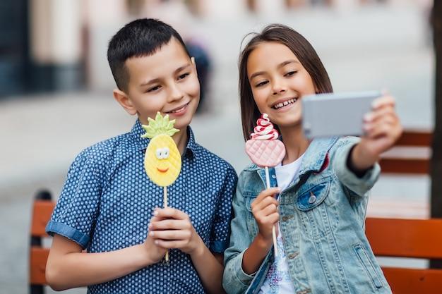 Foto von zwei glücklichen kindern, die an einem sommertag selfie mit süßigkeiten an den händen machen und lächeln.