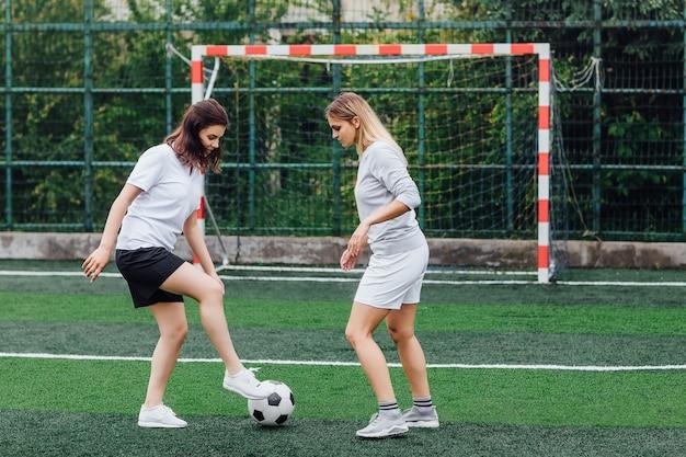 Foto von zwei hübschen frauen, die zusammen auf dem feld fußball spielen