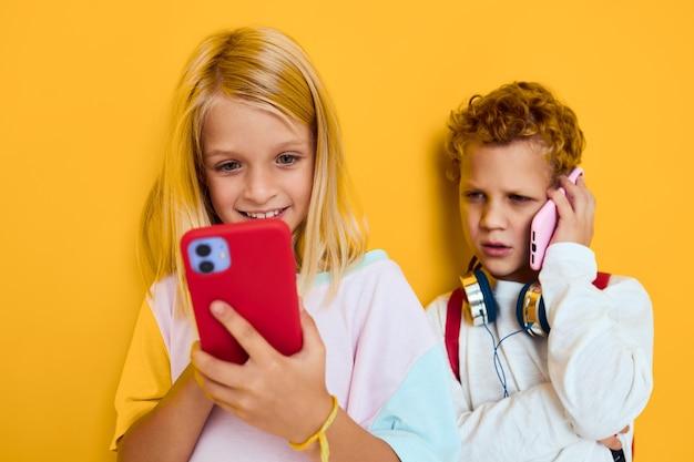 Foto von zwei kleinen kindermädchen, die den isolierten hintergrund der telefonunterhaltungskommunikation betrachten