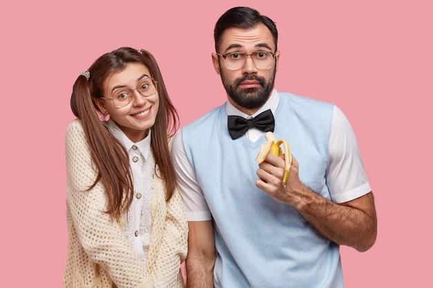Foto von zwei klugen fröhlichen freunden treffen sich während des freien tages, posieren vor der kamera, essen banane, tragen brille