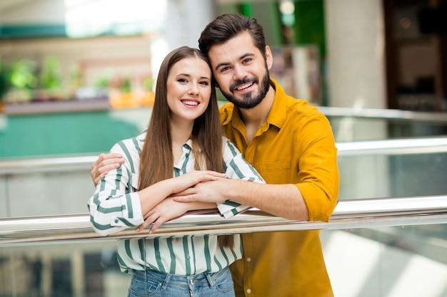 Foto von zwei leuten, fröhliche hübsche dame, gutaussehender mann, paar genießt freizeit-einkaufszentrum-wochenende, die schiefe handläufe umarmt, tragen lässiges jeans-hemd-outfit im innenbereich