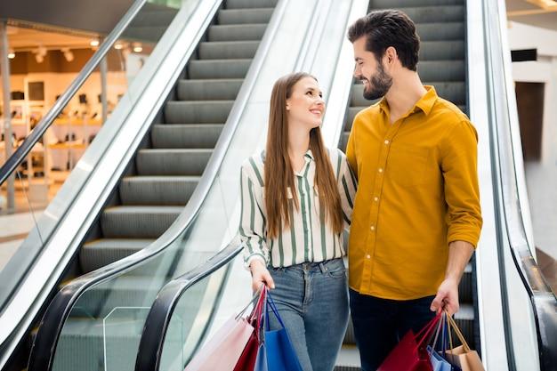 Foto von zwei leuten jubeln attraktive dame hübscher kerl paar genießen freizeit kaufen viele taschen tragen rolltreppe einkaufszentrum umarmung blick augen tragen lässiges jeanshemd outfit drinnen