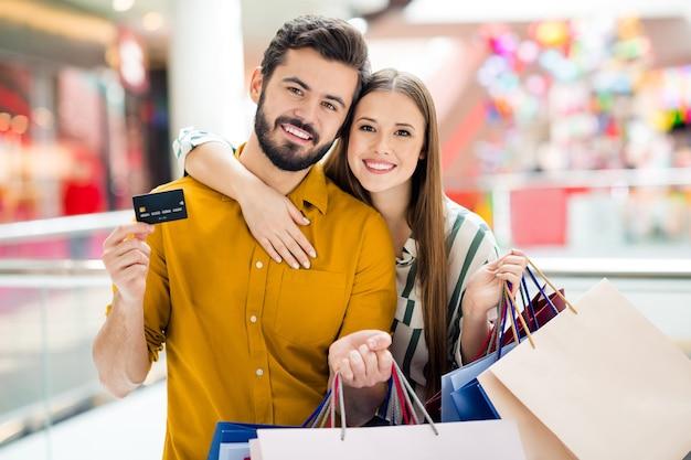 Foto von zwei personen, fröhliche dame, gutaussehender mann, paar genießt freizeit, hält viele taschen, verwendet kreditkarten-gehalts-einkaufszentrum, umarmt lässiges jeanshemd-outfit drinnen