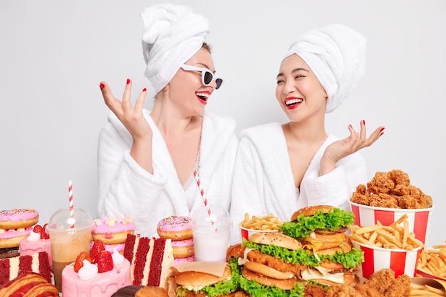 Foto von zwei positiven frauen, die sich glücklich ansehen, fröhliche stimmung haben, zeit zu hause verbringen, umgeben von viel junk-food, ungesunde essgewohnheiten haben, leckere kalorienreiche snacks essen.
