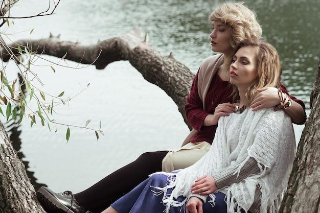 Foto von zwei schönen frauen, die auf einem baum nahe see aufwerfen.
