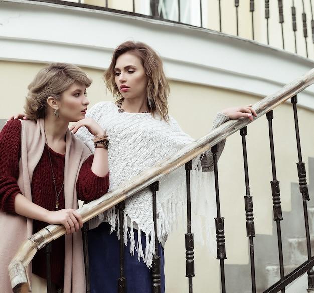 Foto von zwei schönen frauen, die auf einer treppe posieren