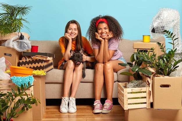Foto von zwei schönen verschiedenen studentinnen wechseln den wohnort
