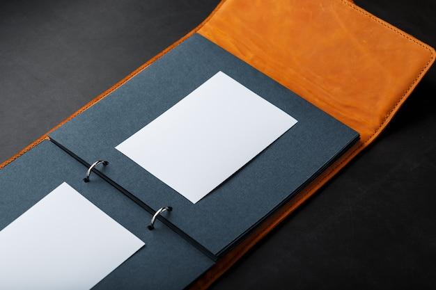 Fotoalbum mit leerem platz für fotos, weiße rahmen auf schwarzem papier.