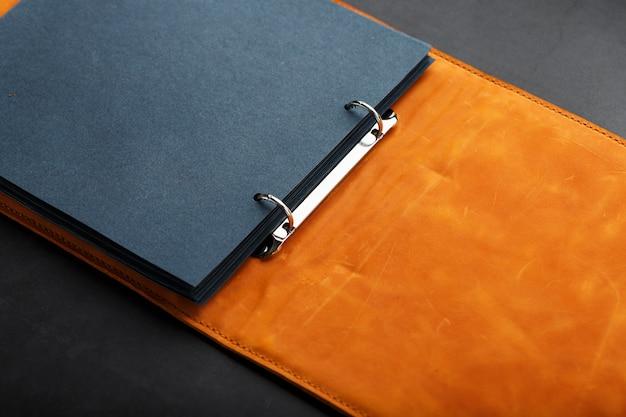 Fotoalbum mit leerem schwarz für fotos. geteilte ringe für makroalben in nahaufnahme. das albumcover besteht aus braunem, handgefertigtem echtleder