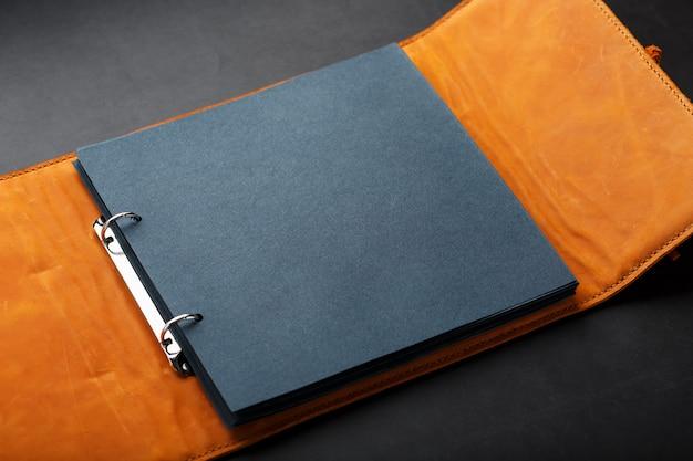 Fotoalbum mit leerem schwarz für fotos. geteilte ringe für makroalben in nahaufnahme. das albumcover besteht aus braunem, handgefertigtem echtleder.