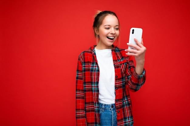 Fotoaufnahme der attraktiven positiven gut aussehenden jungen frau, die lässiges stilvolles outfit poising trägt