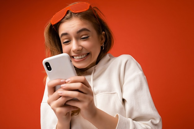 Fotoaufnahme der attraktiven überglücklichen glücklichen positiven gut aussehenden jungen frau, die lässig stilvoll trägt