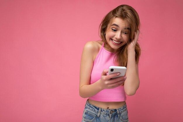 Fotoaufnahme der attraktiven überglücklichen verrückten positiven positiven gut aussehenden jungen frau, die lässig stilvoll trägt