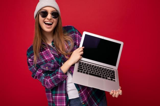 Fotoaufnahme der erstaunlichen lustigen glücklichen schönen lächelnden dunkelblonden jungen frau, die computerlaptop hält