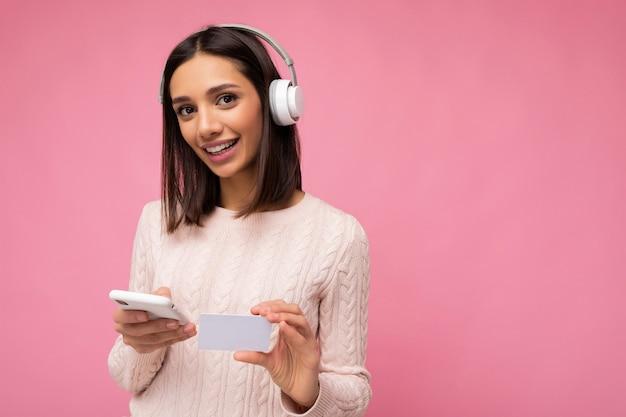 Fotoaufnahme der schönen freudigen lächelnden jungen weiblichen person, die stilvolles lässiges outfit isoliert trägt
