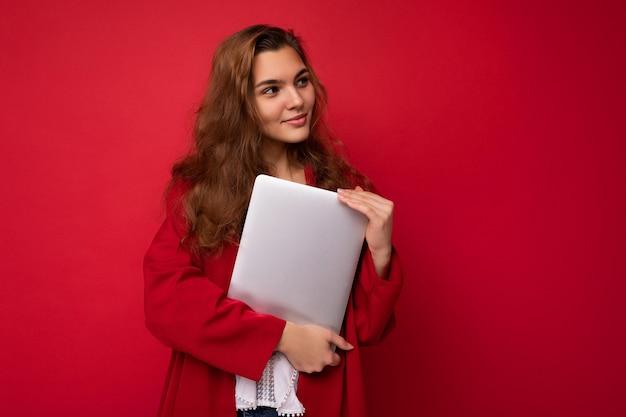 Fotoaufnahme der schönen lächelnden glücklichen jungen brunetfrau, die nahen computerlaptop trägt, der rote strickjacke und weiße bluse trägt, die zur seite lokalisiert über rotem hintergrund schaut.