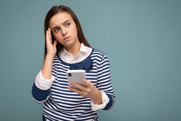 Fotoaufnahme des attraktiven denkens wehmütig gut aussehende junge dame, die lässiges stilvolles outfit trägt