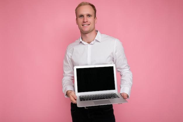Fotoaufnahme des hübschen blonden mannes, der computer-laptop mit leerem monitorbildschirm mit modell und kopierraum hält, der weißes hemd trägt, das kamera betrachtet, die auf netbook lokalisiert über rosa hintergrund zeigt.
