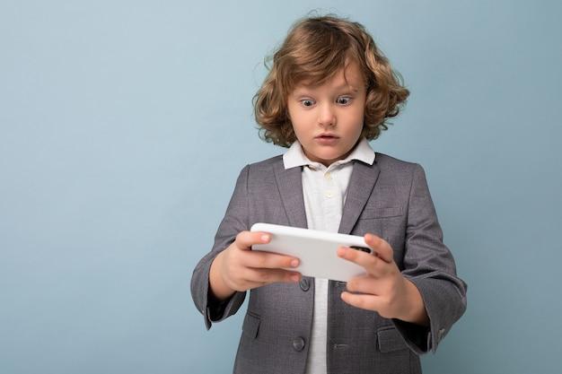 Fotoaufnahme des hübschen emotionalen kinderjungen mit dem lockigen haar, der grauen anzug hält, der telefon hält und verwendet