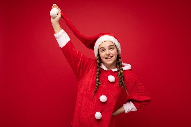 Fotoaufnahme des schönen glücklichen positiven lächelnden brünetten mädchens mit zöpfen, die weihnachtsmannklauselkleidung lokalisiert über roter hintergrundwand tragen kamera betrachten und spaß haben.