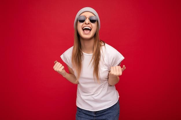 Fotoaufnahme einer attraktiven, fröhlichen, fröhlichen jungen blonden weiblichen person, die auf rotem hintergrund isoliert ist