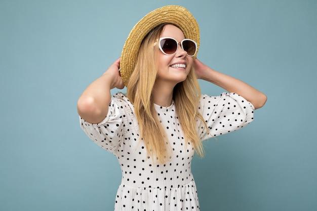 Fotoaufnahme einer attraktiven, glücklich lächelnden jungen blonden frau, die sommerliche freizeitkleidung trägt und stylisch
