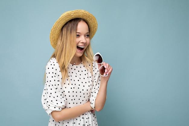Fotoaufnahme einer attraktiven, glücklich lächelnden jungen blonden frau, die sommerliche freizeitkleidung und eine stylische sonnenbrille trägt, die über einer bunten hintergrundwand isoliert ist und zur seite schaut