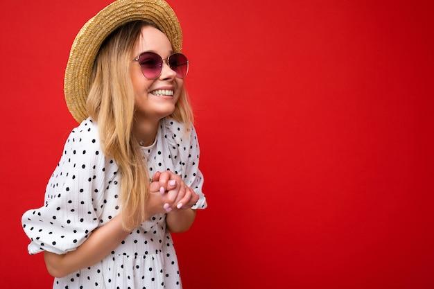 Fotoaufnahme einer attraktiven, glücklich lächelnden jungen blonden frau, die sommerliche freizeitkleidung und stylische sonnenbrillen trägt, einzeln über bunter hintergrundwand, die zur seite schaut. platz kopieren