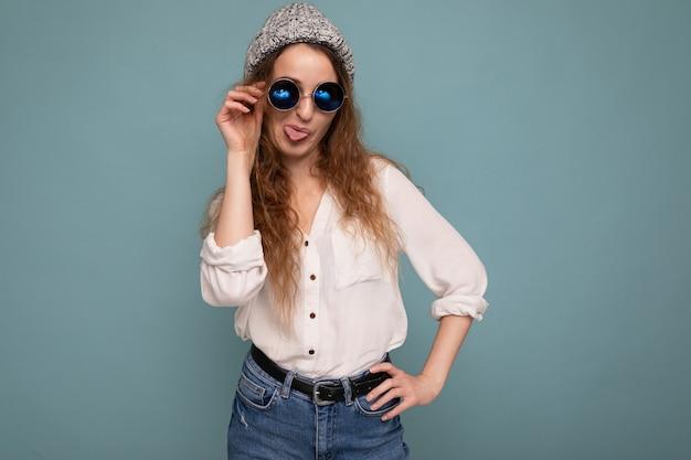 Fotoaufnahme einer attraktiven, glücklichen jungen lockigen frau, die auf blauem hintergrund isoliert ist und eine lässige weiße bluse und eine stilvolle brille trägt, die in die kamera schaut und spaß hat