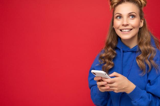 Fotoaufnahme einer attraktiven, gut aussehenden jungen frau, die ein lässiges, stylisches outfit trägt, das auf dem hintergrund isoliert ist, mit leerem raum in der hand und mit handy-messaging-sms nach oben schauend