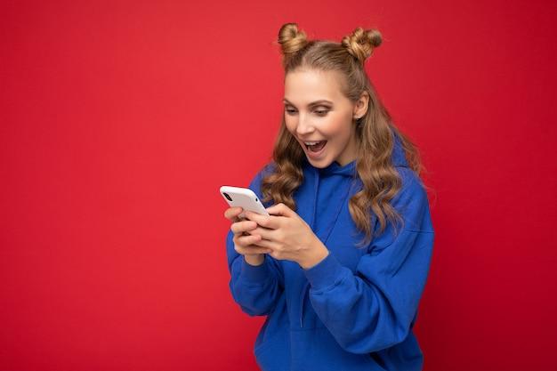 Fotoaufnahme einer attraktiven, positiv gut aussehenden jungen frau, die ein lässiges, stylisches outfit trägt, das auf dem hintergrund isoliert ist, mit leerem raum in der hand und mit handy-messaging-sms-loo