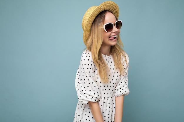 Fotoaufnahme einer attraktiven, sexy, glücklich lächelnden jungen blonden frau, die sommerliche freizeitkleidung und eine stylische sonnenbrille trägt, isoliert über der bunten hintergrundwand, die zur seite schaut.