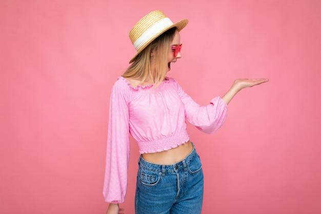 Fotoaufnahme einer attraktiven, überraschten, glücklich lächelnden jungen blonden frau, die sommerliche freizeitkleidung und eine stylische sonnenbrille trägt, einzeln auf einer bunten hintergrundwand, die zur seite schaut.
