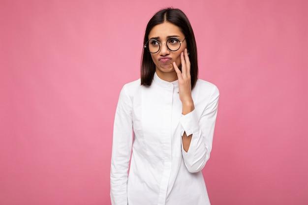 Fotoaufnahme einer attraktiven verärgerten traurigen unzufriedenen jungen brünetten weiblichen person, die ein weißes hemd und eine stilvolle optische brille trägt, einzeln auf rosafarbenem hintergrund, der zur seite schaut.