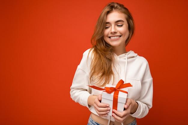 Fotoaufnahme einer charmanten glücklichen, fröhlichen lächelnden blonden jungen frau, die über buntem hintergrund isoliert ist?