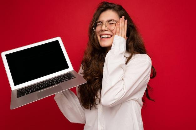 Fotoaufnahme einer erstaunlichen lustigen, glücklichen, schönen lächelnden jungen frau, die computer-laptop mit leerem bildschirm mit mock-up und kopienraum mit weißem hemd isoliert über rotem wandhintergrund hält.