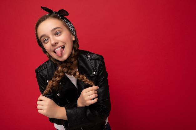 Fotoaufnahme einer hübschen, positiv lächelnden, brünetten, kleinen teenagerin mit zöpfen, die eine stilvolle schwarze lederjacke und ein weißes t-shirt trägt, das isoliert über einer roten hintergrundwand steht und spaß hat und sho