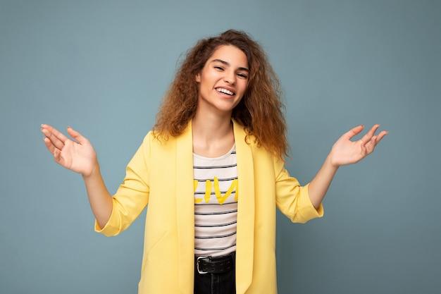 Fotoaufnahme einer jungen lächelnden, glücklichen, attraktiven, brünetten, lockigen frau mit aufrichtigen emotionen