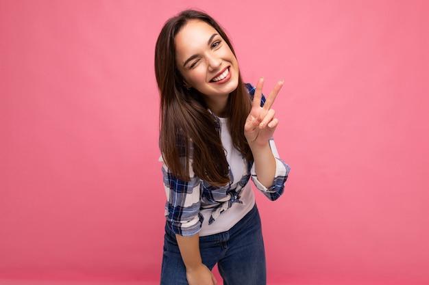 Fotoaufnahme einer jungen positiven entzückenden lächelnden hübschen brünetten frau mit aufrichtigen emotionen, die ein hipster-check-shirt trägt, das isoliert auf rosafarbenem hintergrund mit freiem platz steht und ein friedenszeichen zeigt.