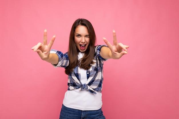 Fotoaufnahme einer jungen positiven entzückenden lächelnden hübschen brünetten frau mit aufrichtigen emotionen