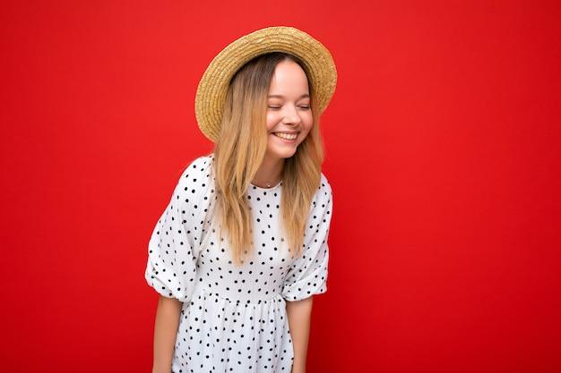 Fotoaufnahme einer jungen, schönen, süßen, glücklichen blonden frau, die ein lässiges kleid und einen strohhut trägt, isoliert