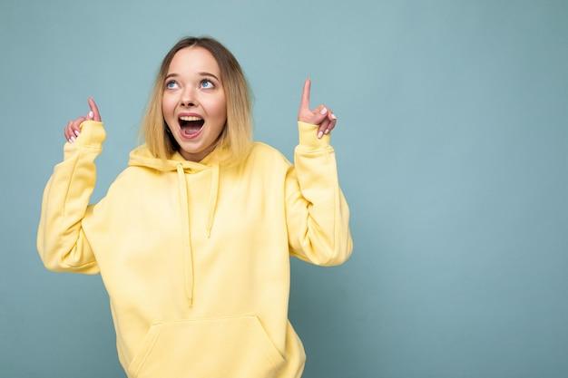 Fotoaufnahme einer jungen, schönen, süßen, glücklichen blonden frau, die einen stylischen gelben hoodie trägt, isoliert über