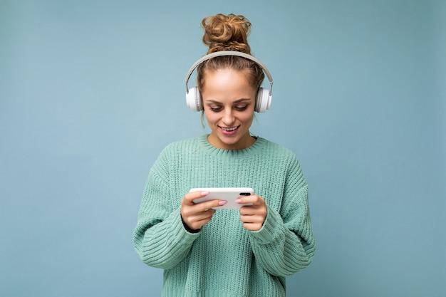 Fotoaufnahme einer schönen, fröhlich lächelnden jungen weiblichen person, die ein stilvolles, lässiges outfit trägt, isoliert