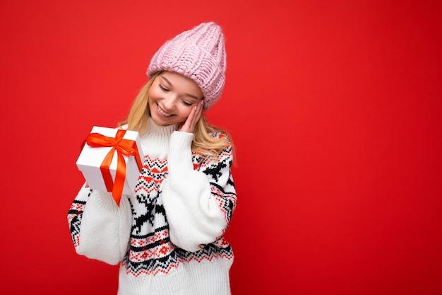 Fotoaufnahme einer schönen, glücklich lächelnden, erstaunten jungen blonden frau, die über einer roten hintergrundwand isoliert ist und einen winterpullover und einen rosa hut trägt, der eine weiße geschenkbox mit rotem band hält. platz kopieren, mockup