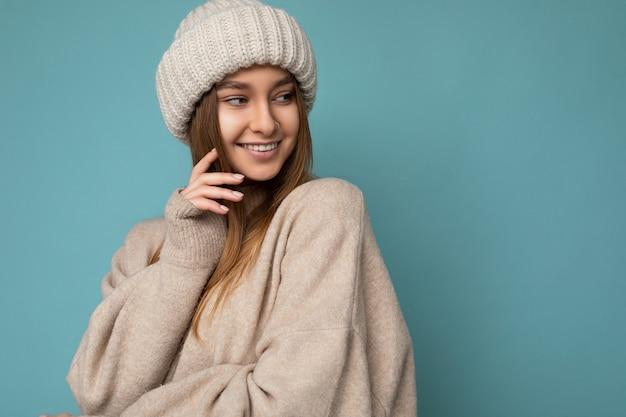 Fotoaufnahme einer schönen, glücklich lächelnden, sexy jungen dunkelblonden frau, die über einer blauen hintergrundwand isoliert ist und einen beigefarbenen warmen pullover und eine gestrickte beige mütze trägt, die zur seite schaut