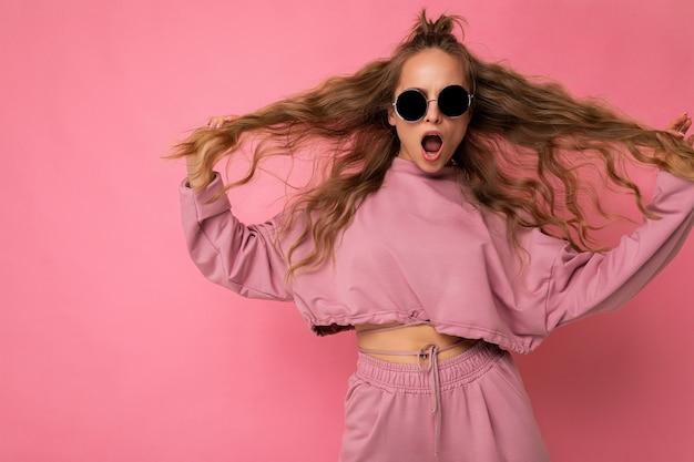 Fotoaufnahme einer schönen glücklichen, amüsanten jungen dunkelblonden, lockigen frau, die über rosafarbenem hintergrund isoliert ist