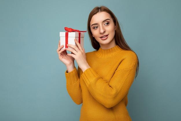 Fotoaufnahme einer schönen, glücklichen, brünetten jungen frau, die über blauer hintergrundwand isoliert ist und einen senffarbenen pullover trägt, der eine weiße geschenkbox mit rotem band hält und zur seite schaut.